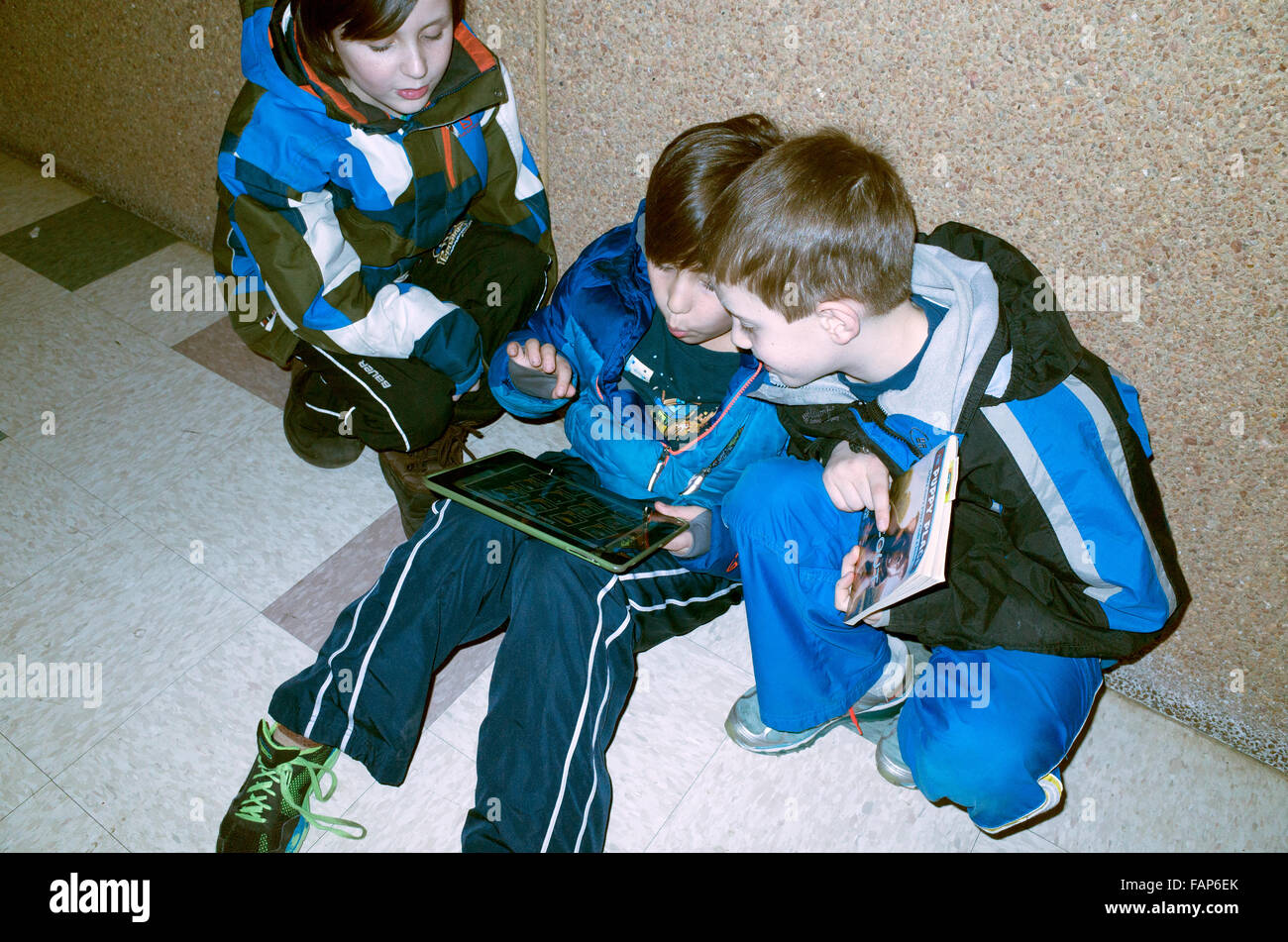 Three boys totally engrossed in playing video game on a tablet. St Paul Minnesota MN USA - Stock Image