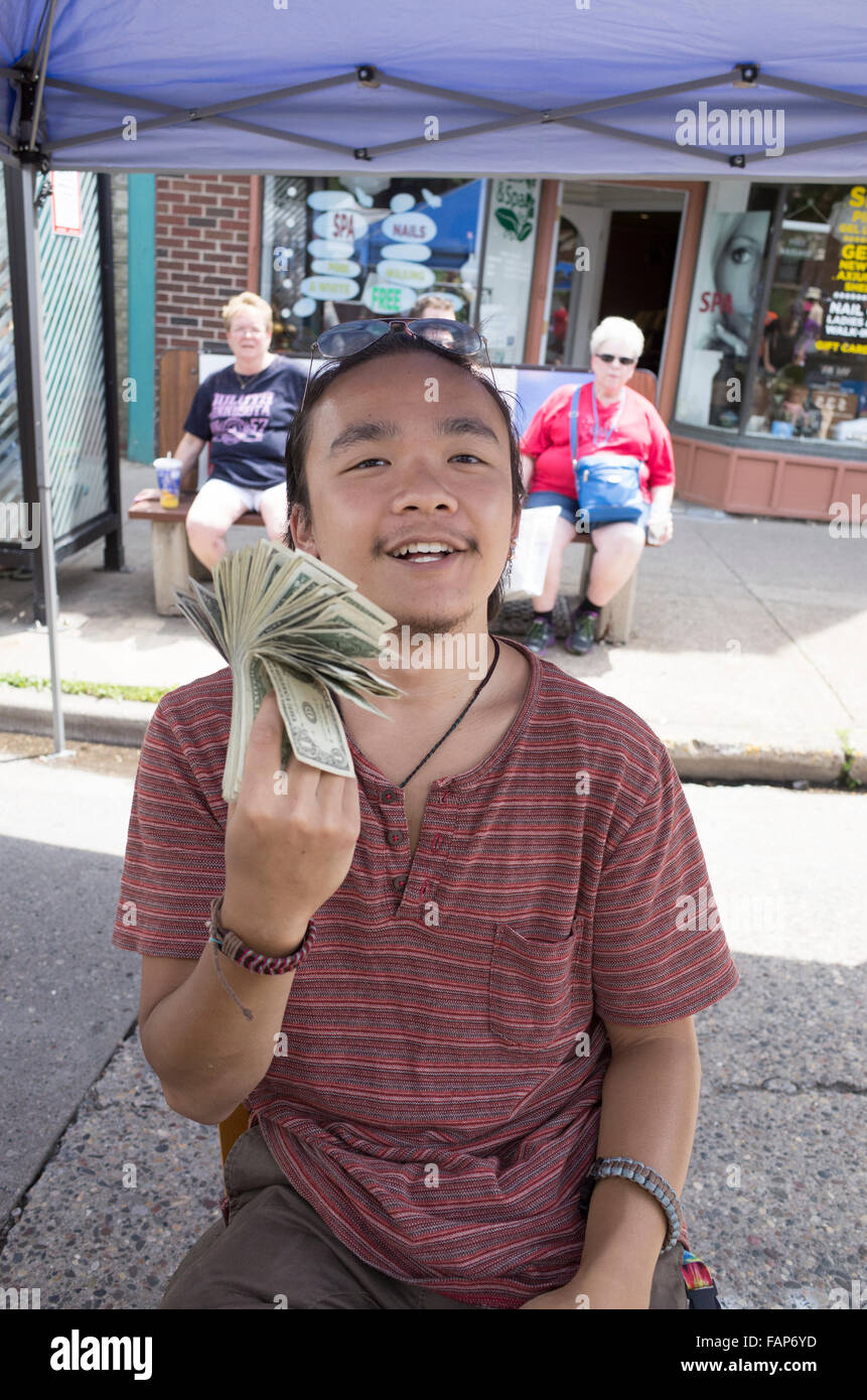 Young Asian American man proudly flips wad of money at his concession booth. Grand Old Day Street Fair. St Paul - Stock Image
