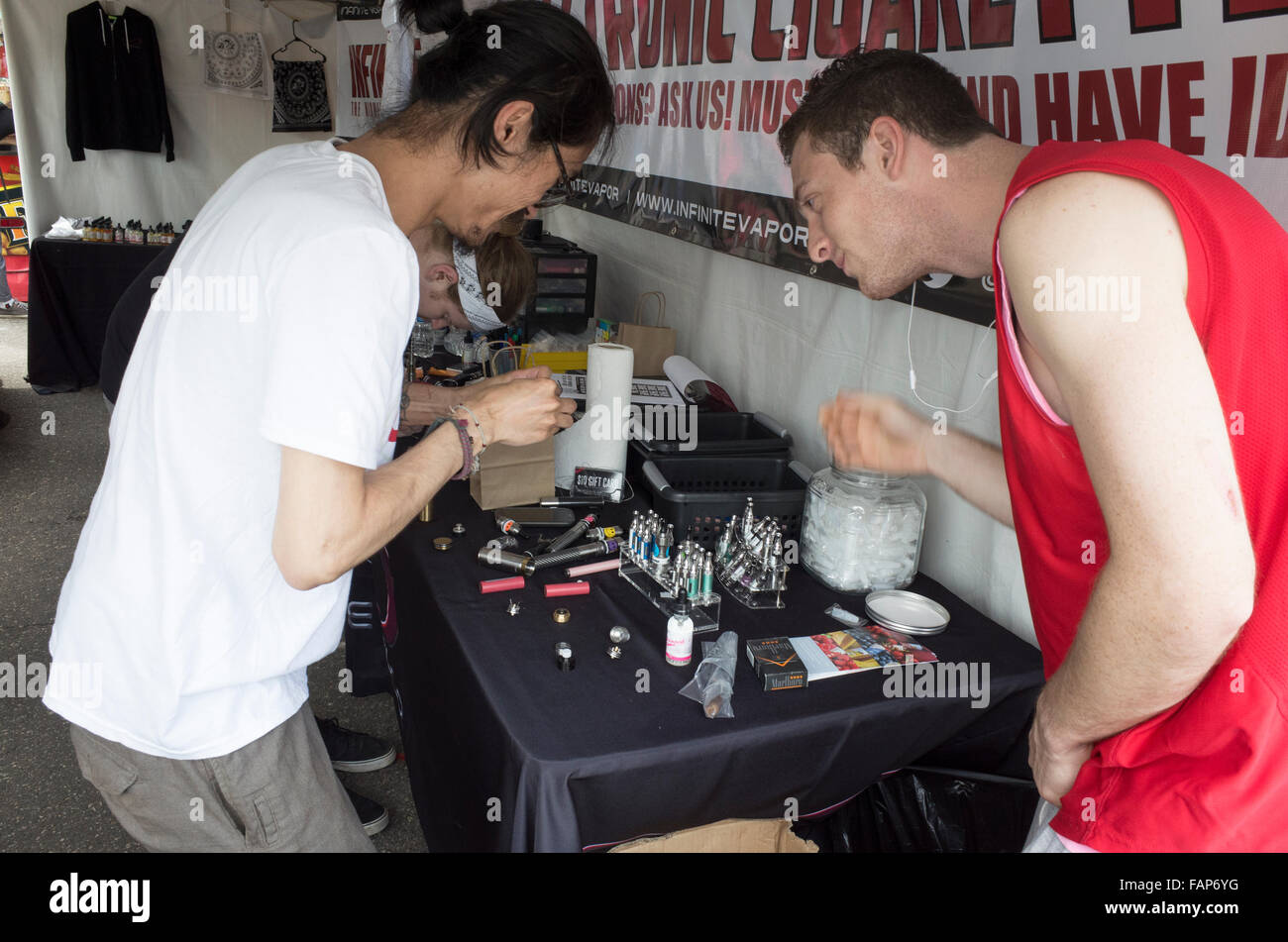 Three men loading e-cigs at the Infinite Vapor concession stand. Grand Old Day Street Fair. St Paul Minnesota MN - Stock Image