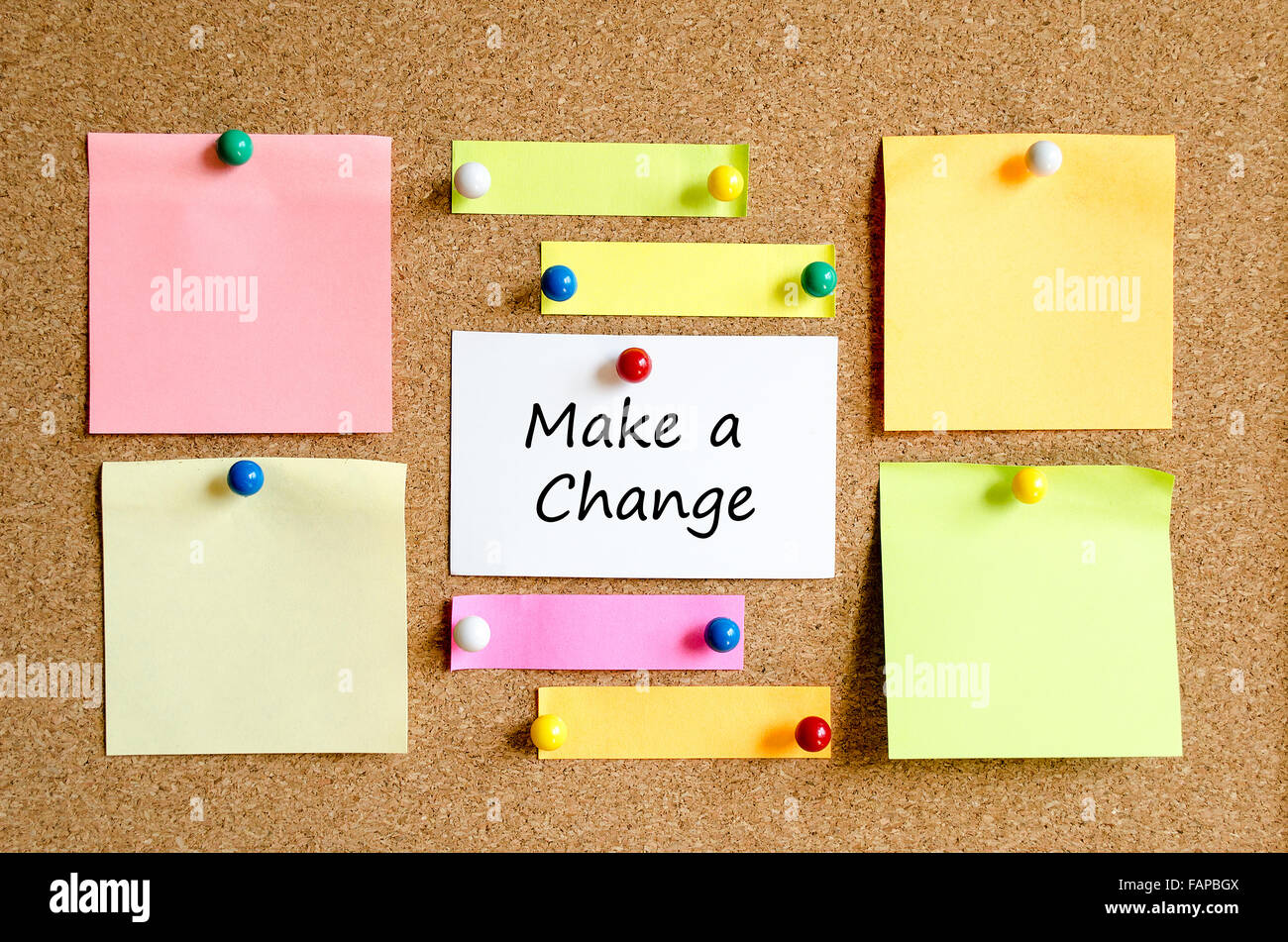 Colorful sticky notes on cork board background and text concept make a change Stock Photo