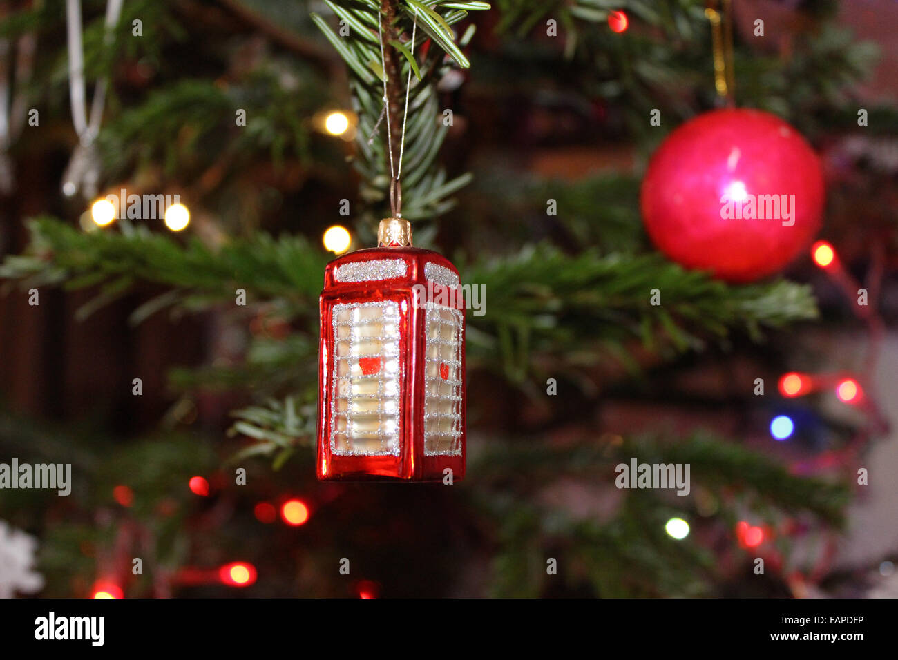 A Christmas decoration, in the form of red telephone box, hangs from a Christmas tree. - Stock Image