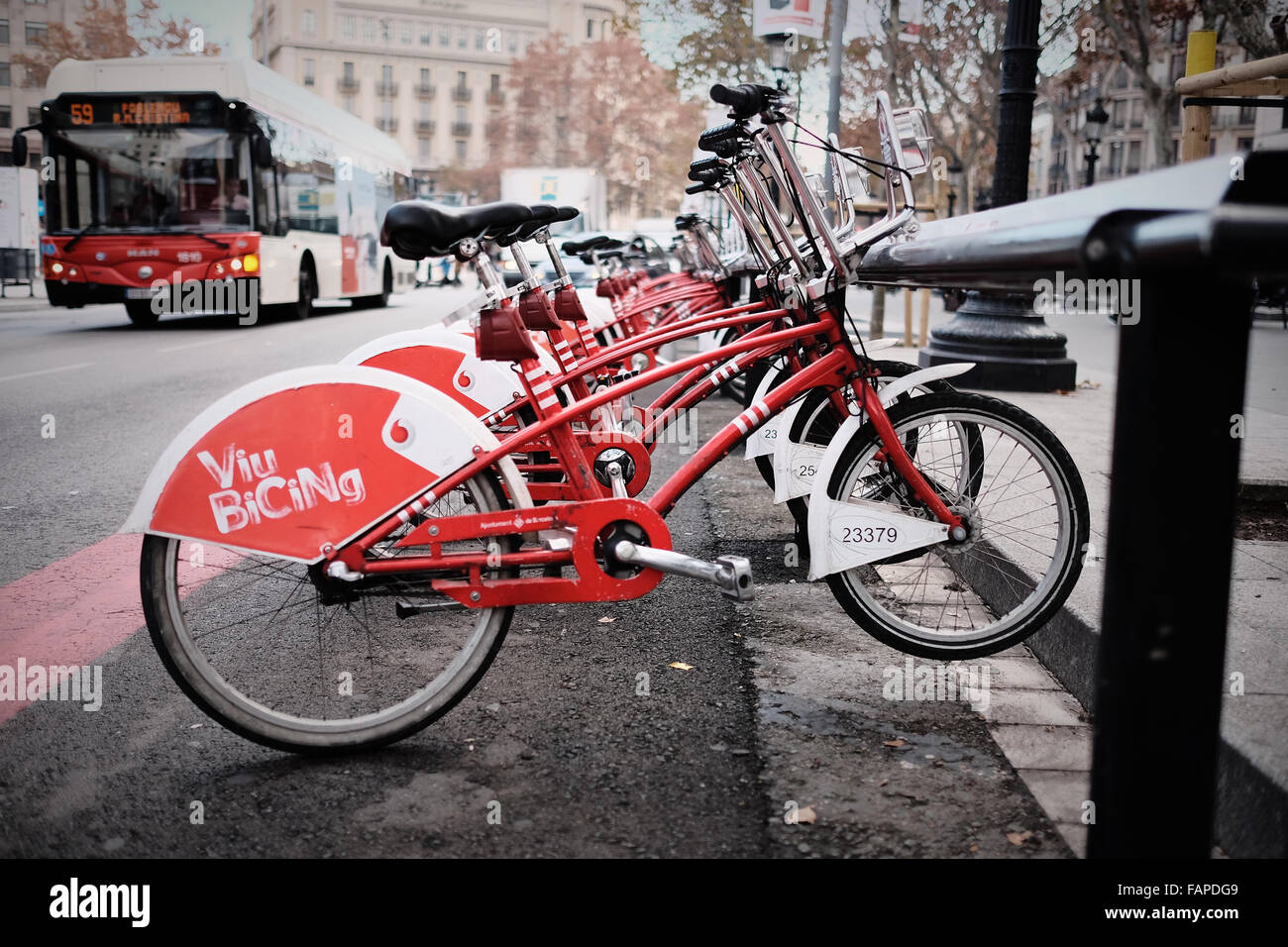 Barcelona rental city bikes and bike stand with bus in background. Public transport. - Stock Image