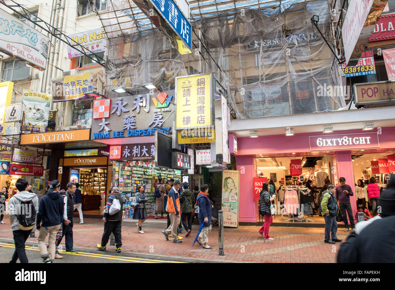 People shop in one of the busiest shopping areas in Hong Kong passing the entrance to the bookstore.The bookstore Stock Photo