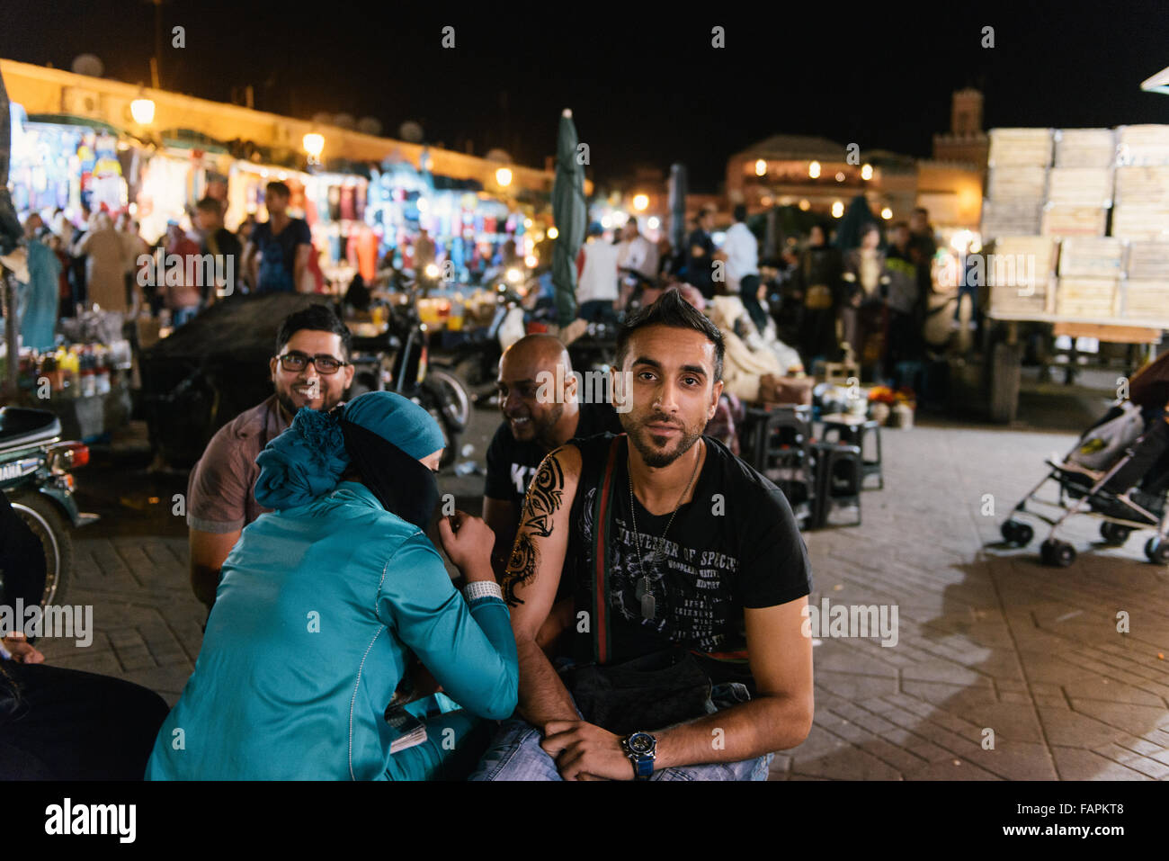 Tourist getting henna tattoo on forearm in Jemaa el Fnaa Square in Marrakech at night - Stock Image