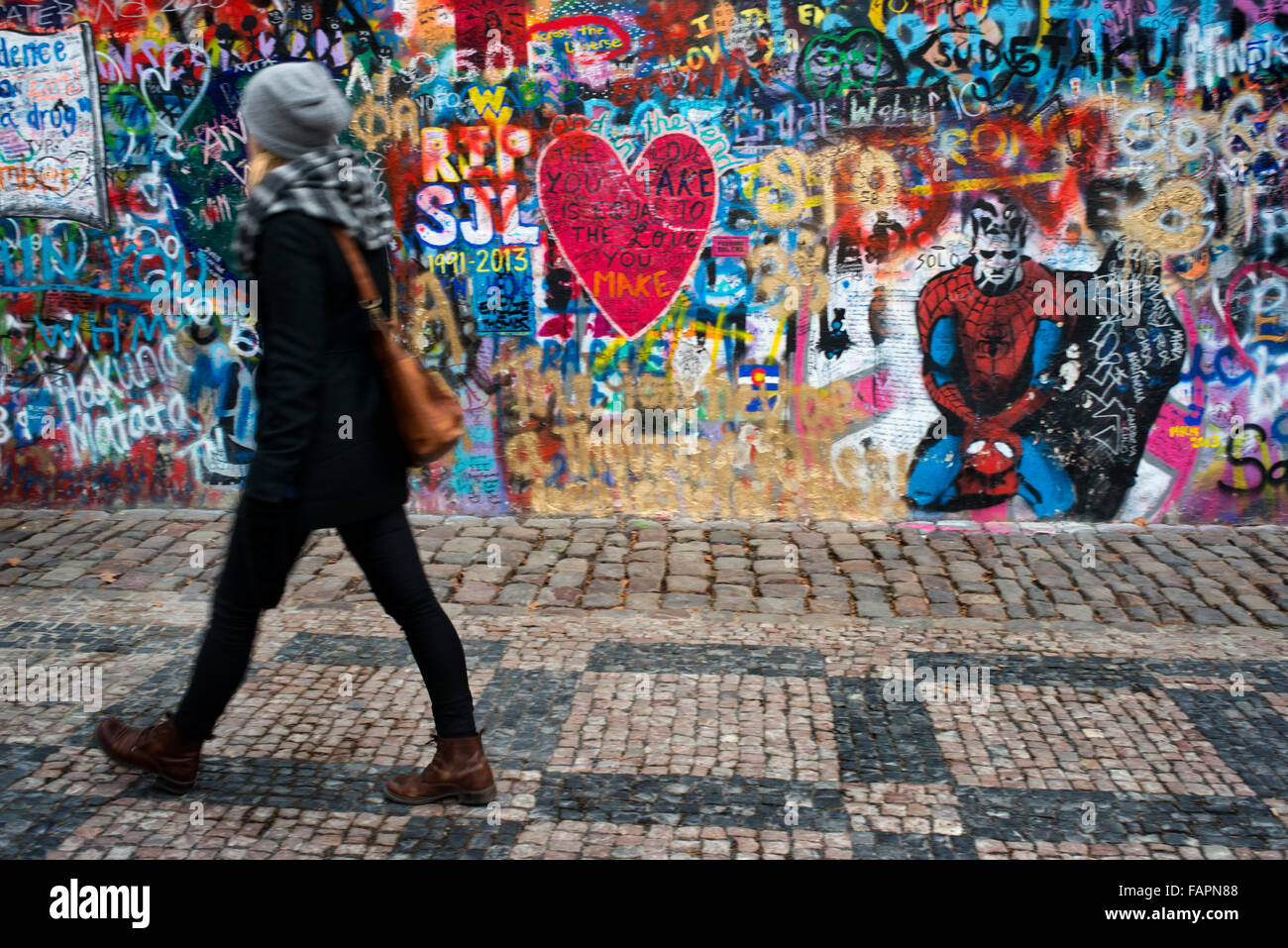 A girl walks past the John Lennon Wall in Prague center . The John Lennon Wall is a wall, which once was one most - Stock Image