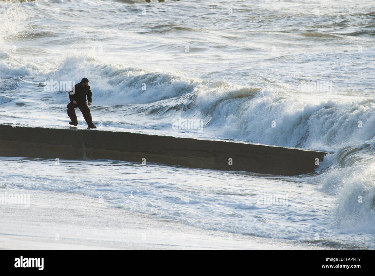Aberystwyth Wales UK Sunday 03 January 2016 A man plays 'dodge the waves' , running along a breakwater or - Stock Image