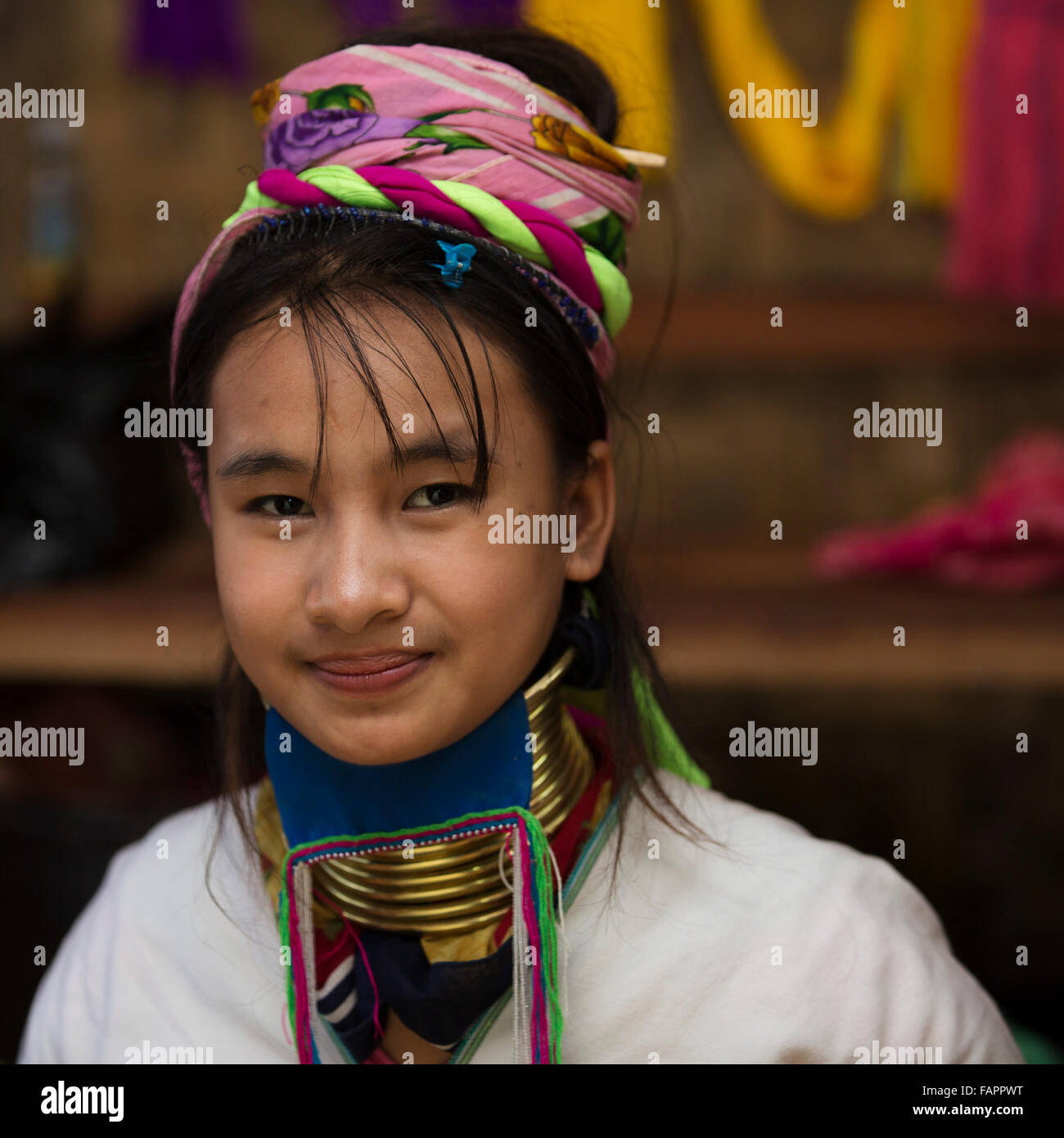A woman from the Kayan tribe weaving in a workshop at Inle Lake in Myanmar (Burma). The woman wears brass coils on her neck. Stock Photo