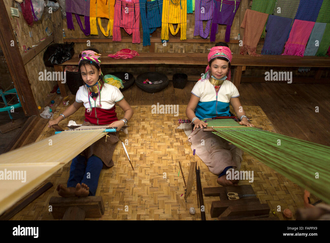 Women from the Kayan tribe weaving in a workshop at Inle Lake in Myanmar (Burma). The women wear brass coils on their necks. Stock Photo