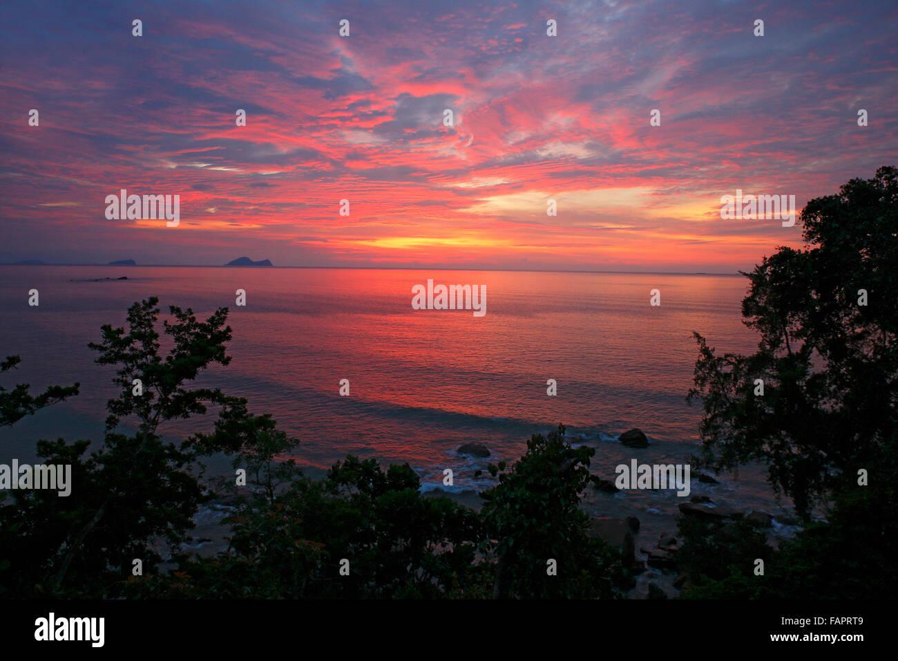 Sunset over the South China Sea, coast at Permai Rainforest, Sarawak, Borneo, Malaysia, Asia - Stock Image