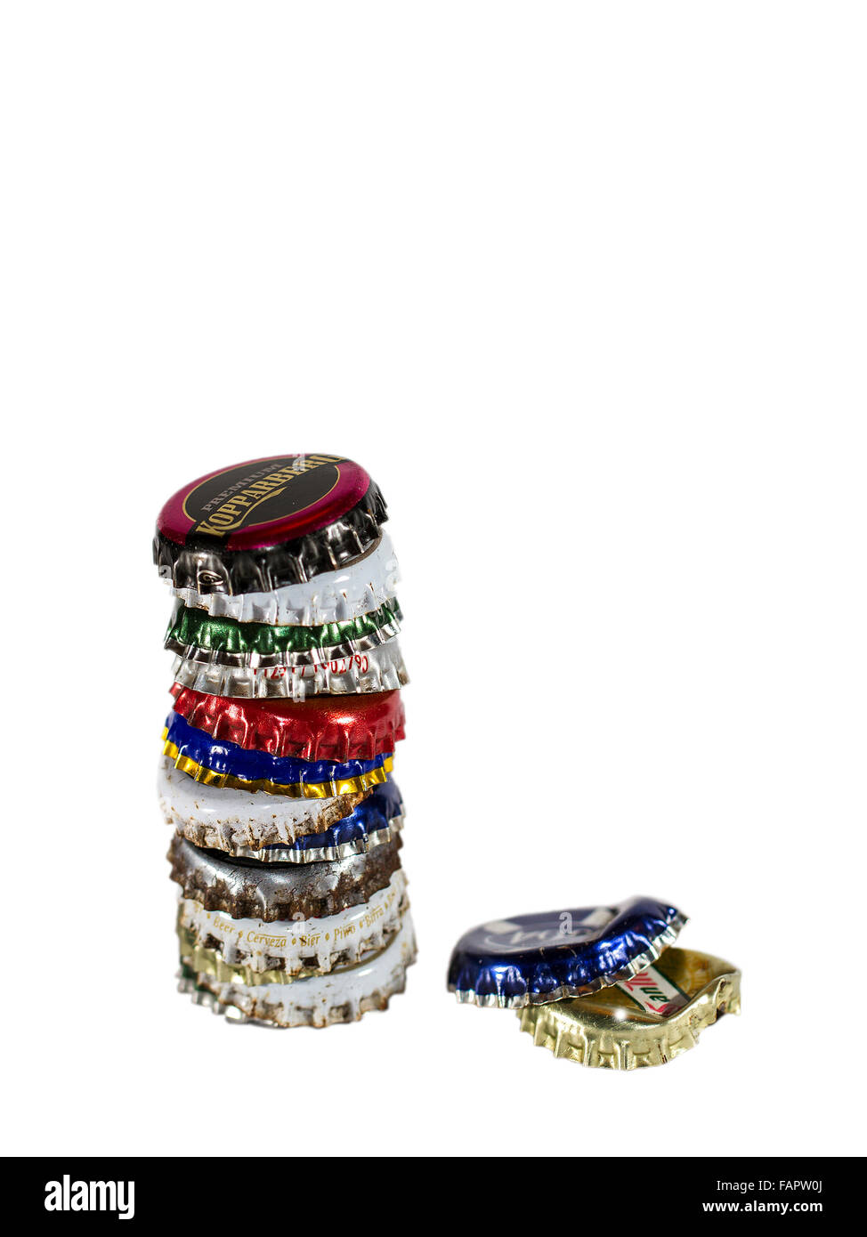 Stack of colourful bottle tops on a white background - Stock Image
