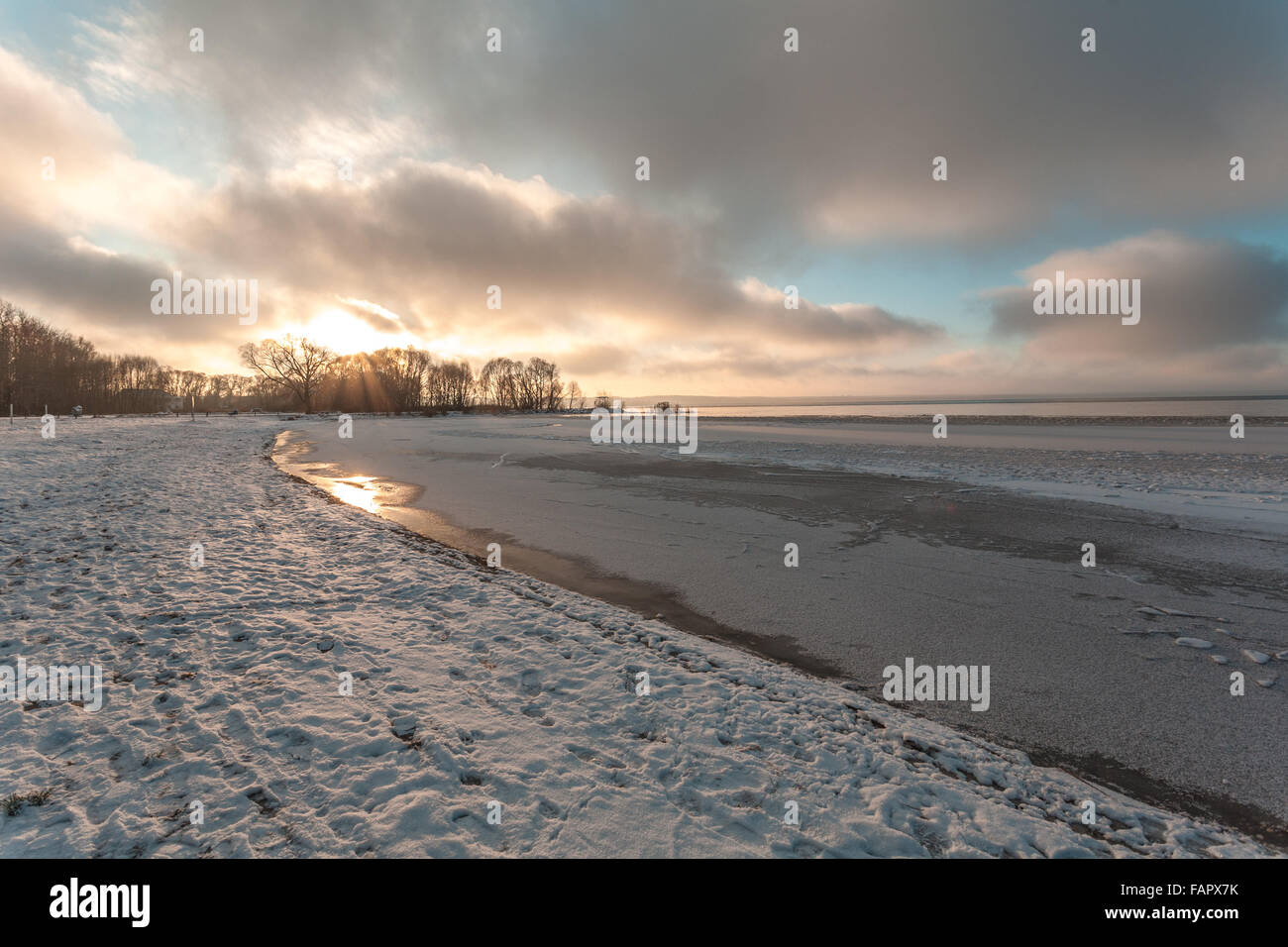 Winter evening on the bank of the lake with the first ice and snow. - Stock Image