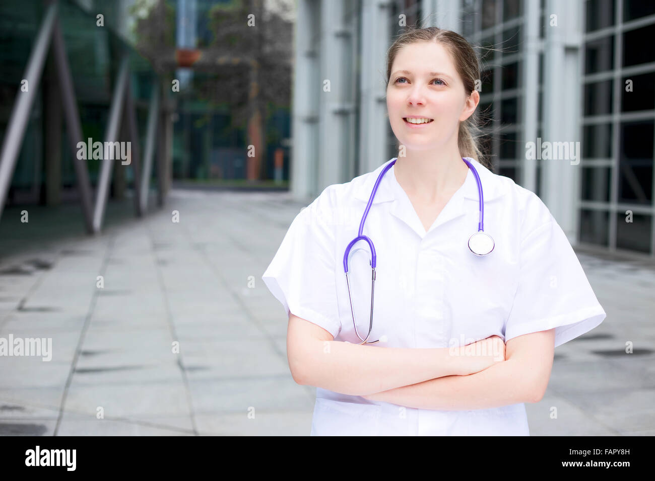 a young doctor standing with her arms crossed - Stock Image