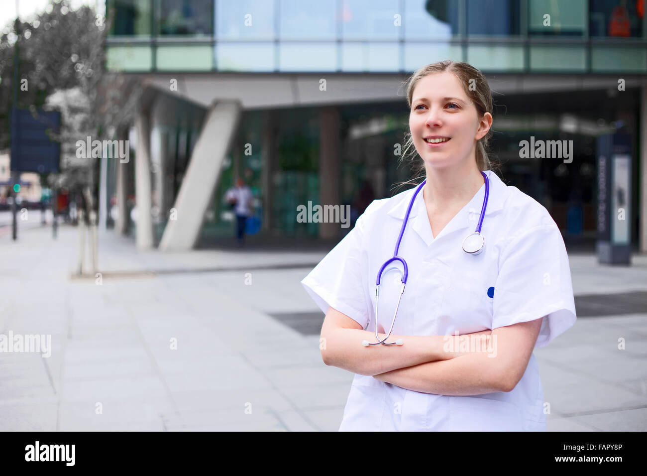 young doctor standing with her arms crossed - Stock Image