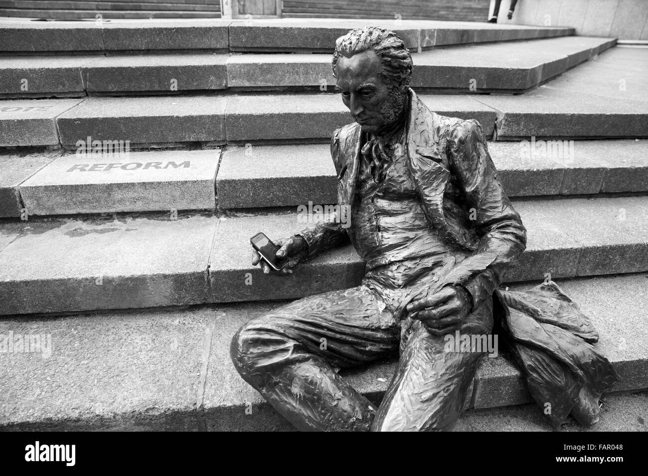 Statue of Thomas Attwood in Chamberlain Square, Birmingham, with mobile phone placed in his right hand. - Stock Image