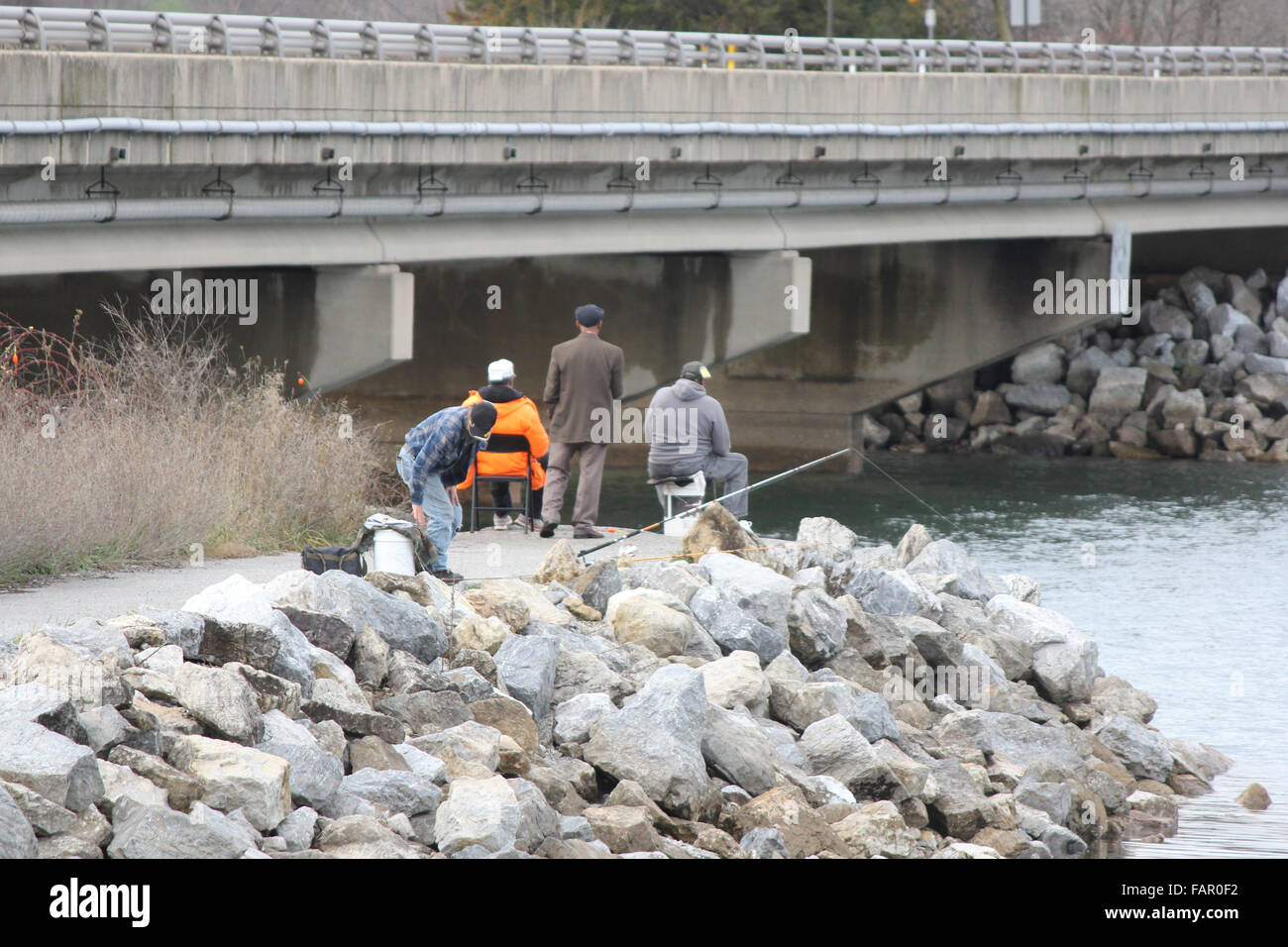 Four older men fishing from a stone landing. All facing away. Unrecognizable - Stock Image