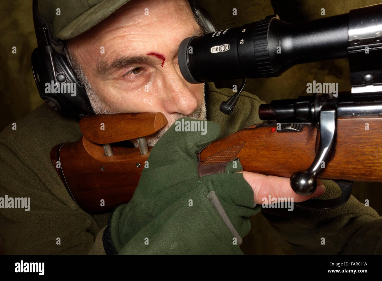 A hunter with 'scope eye' wound shooting  a rifle with telescopic sight. - Stock Image