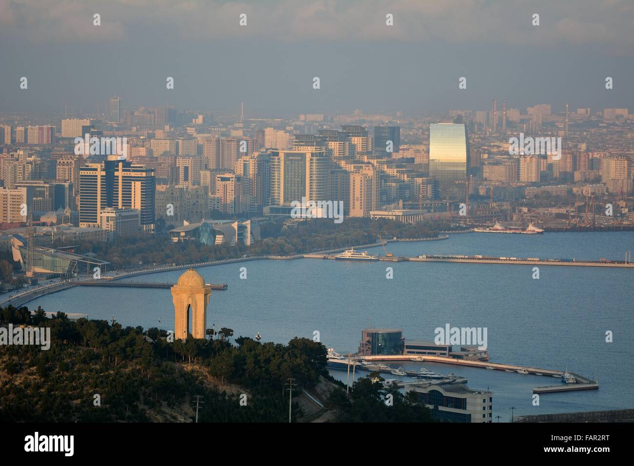 View over Baku, Azerbaijan, and the Caspian Sea, in sunshine with haze showing the 20th January monument in foreground. Stock Photo