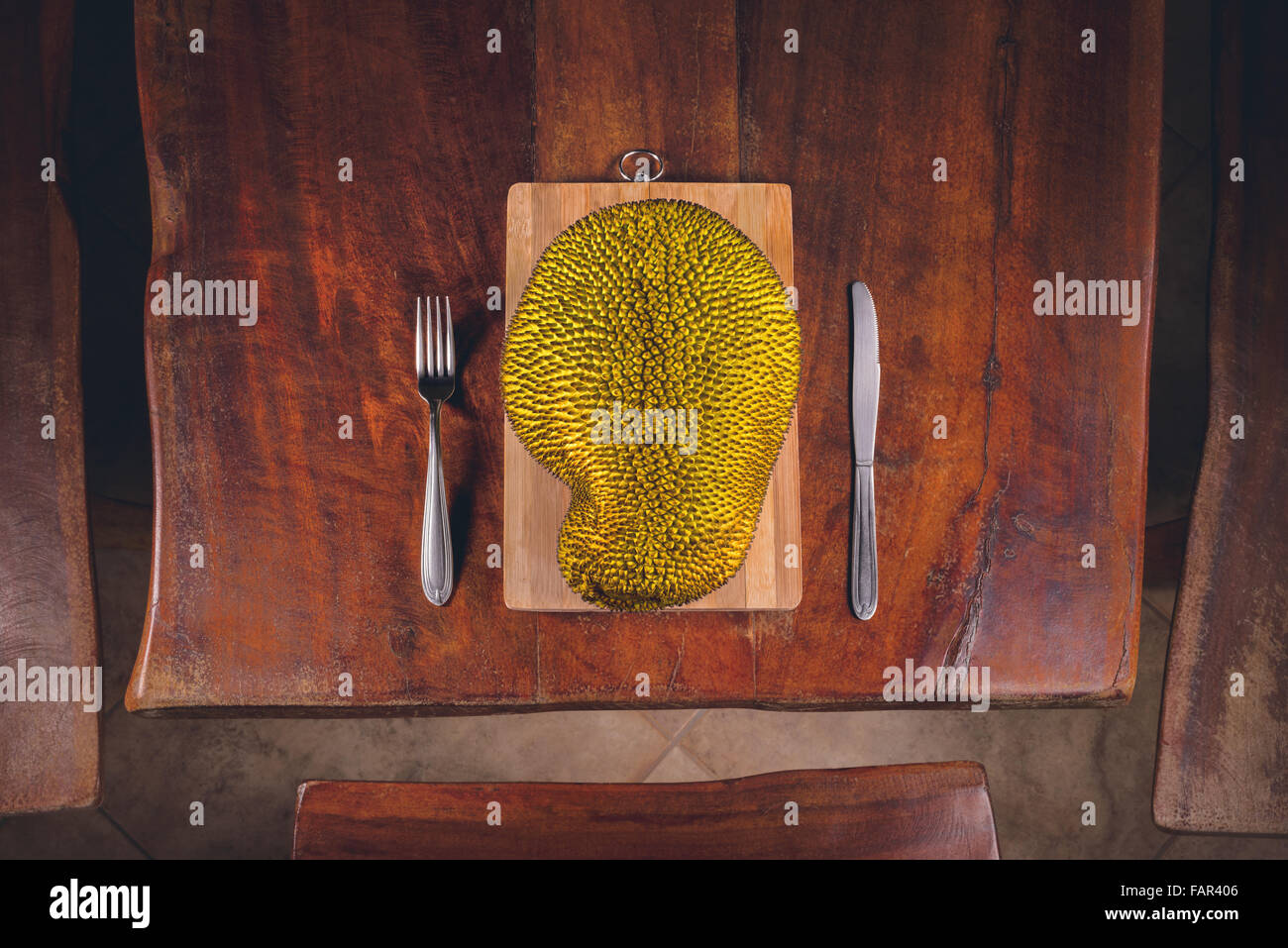 Fruit jackfruit on the table and cutlery around it. - Stock Image