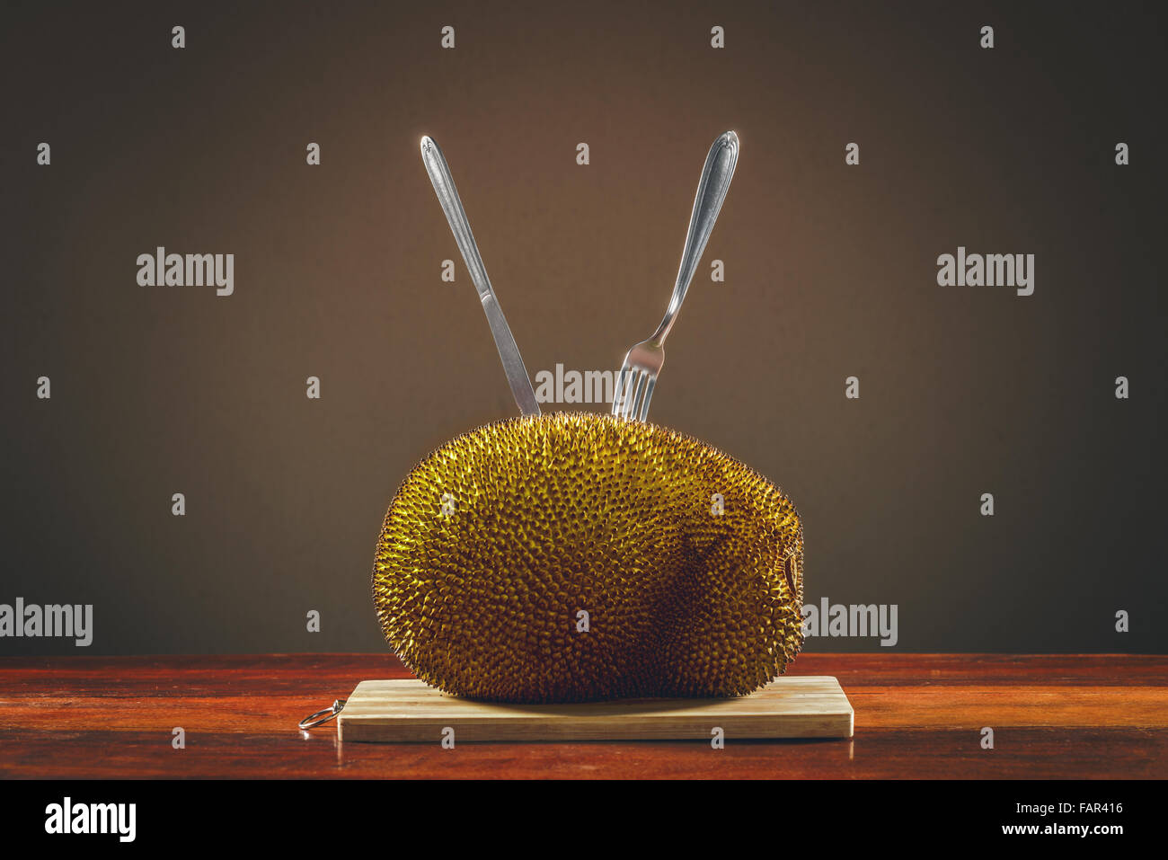 Fruit jackfruit on the table and cutlery stuck on it. - Stock Image