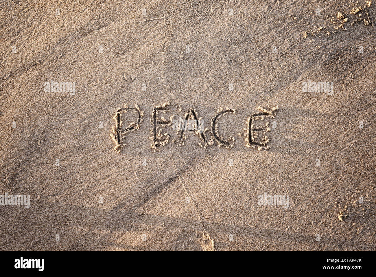 The word peace written in sand. - Stock Image