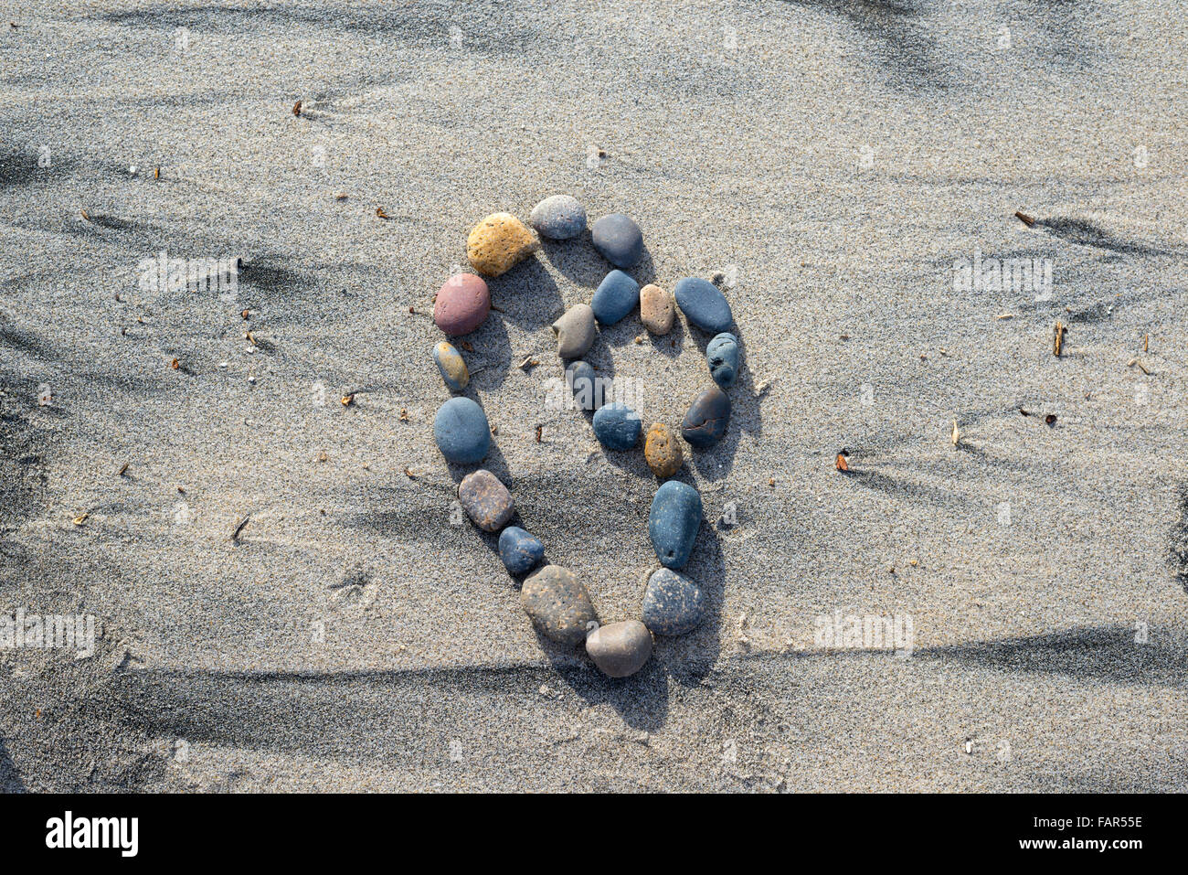 Heart shape formed by stones on sand. - Stock Image