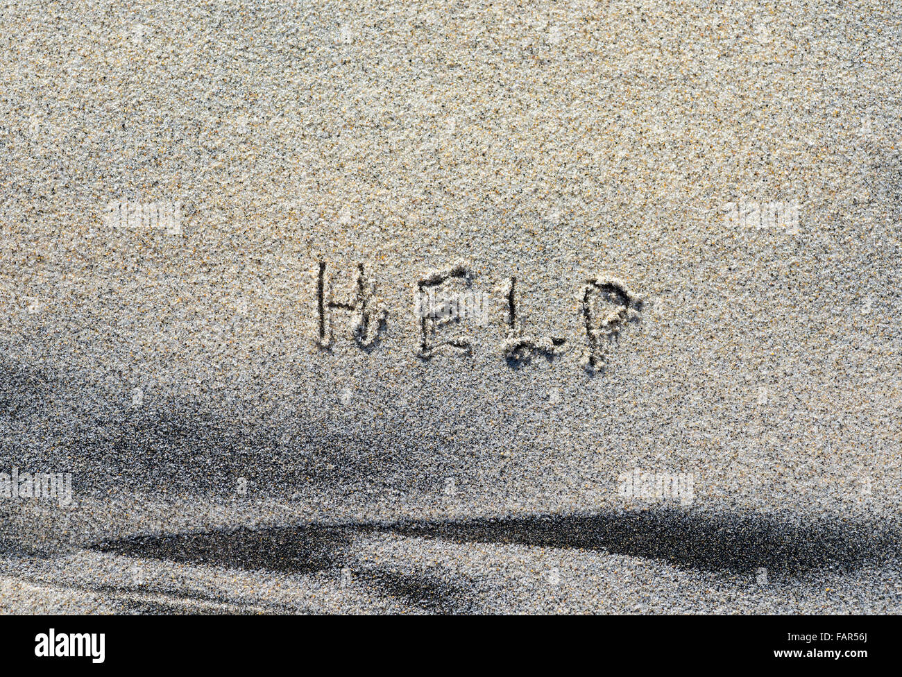 The word HELP written in sand. - Stock Image