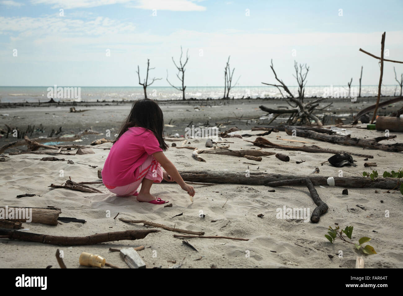 child playing at the polluted beach - Stock Image