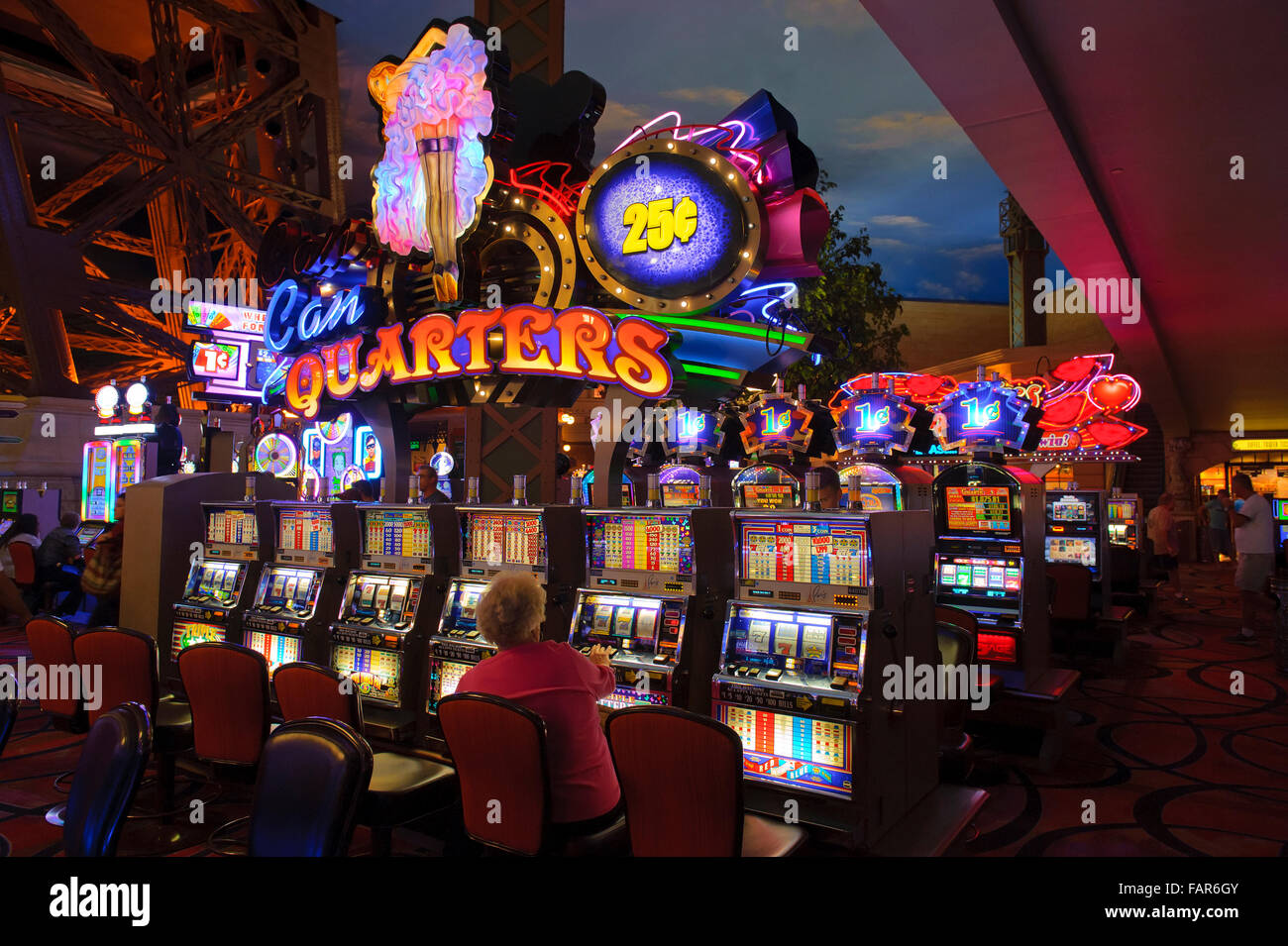 Elderly woman playing a slot machine in the casino of the Paris Hotel, Las Vegas, Nevada. - Stock Image