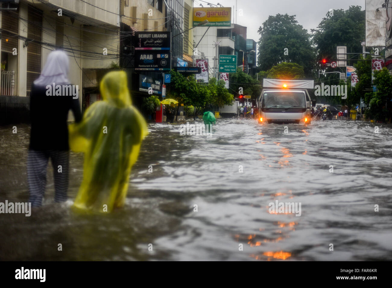 People walking through floodwaters during heavy rain in Jakarta. Stock Photo