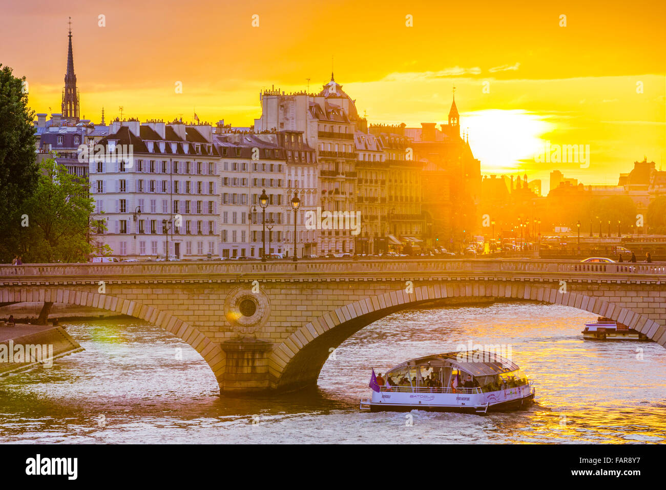 sunset over River Seine and Pont Louis Philippe bridge with river cruise, Paris - Stock Image