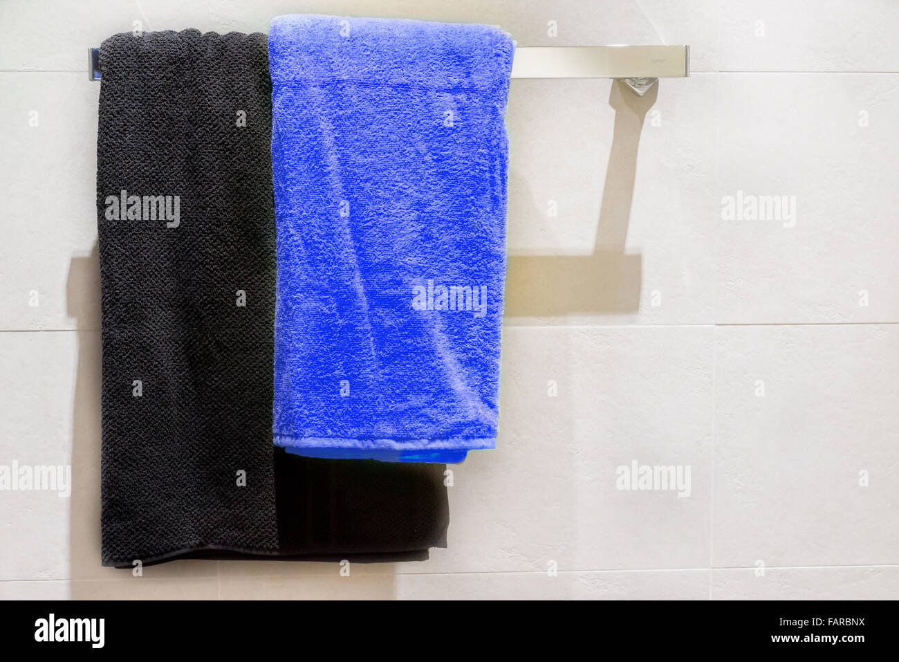 Black and blue towel on hanger in bathroom - Stock Image