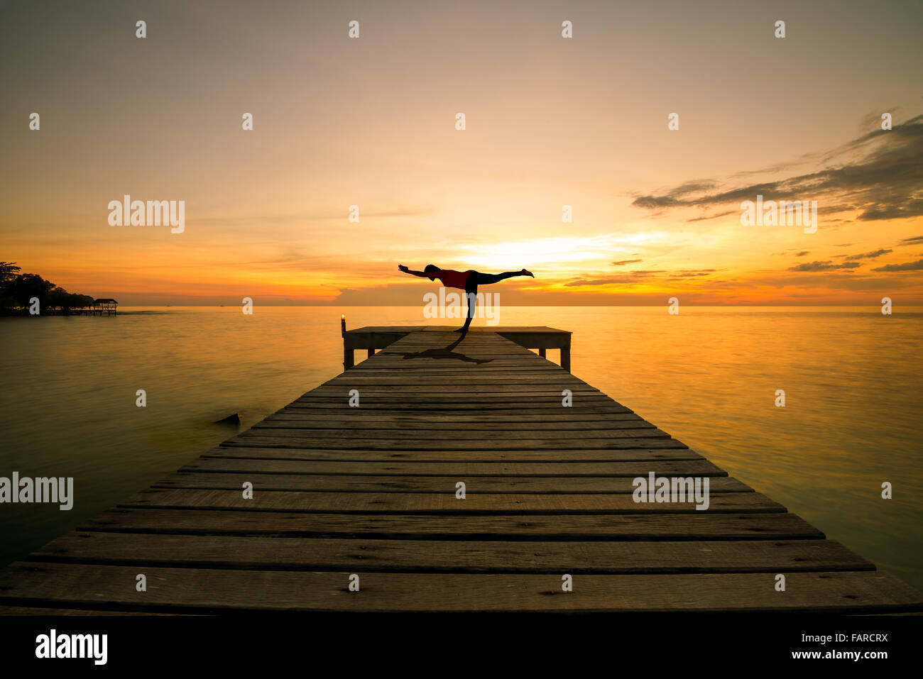 Summer, Travel, Vacation and Holiday concept - Woman silhouette practicing yoga Warrior pose on foot on sea bridge - Stock Image