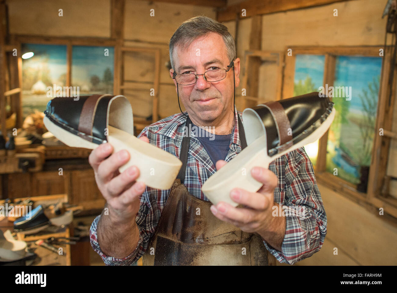 Burg, Germany. 07th Dec, 2015. Manfred Karolczak holds up wooden slippers at his workshop in Burg, Germany, 07 December - Stock Image