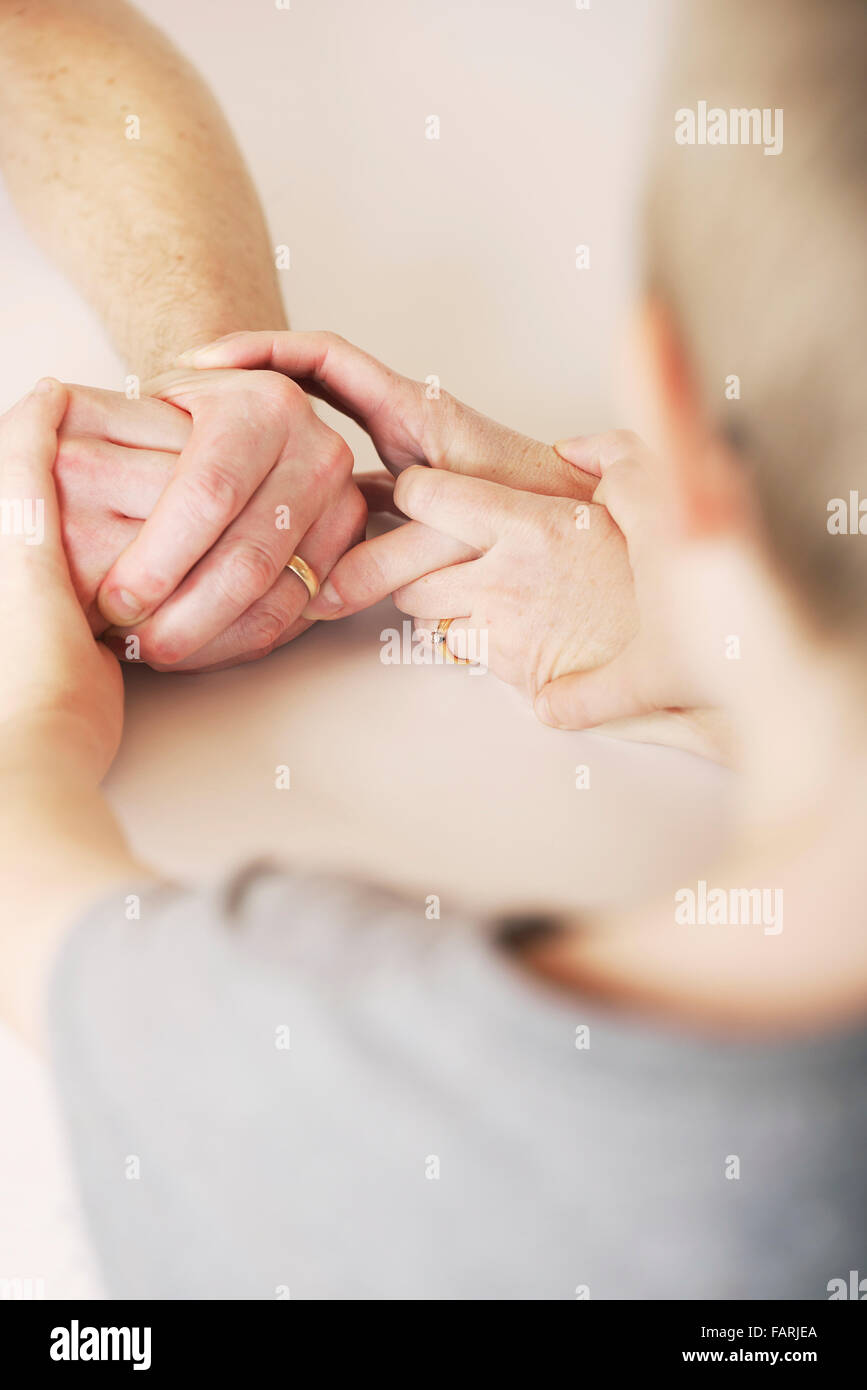 Child holds the hands of mother and father during a fragmented and strained relationship - Stock Image