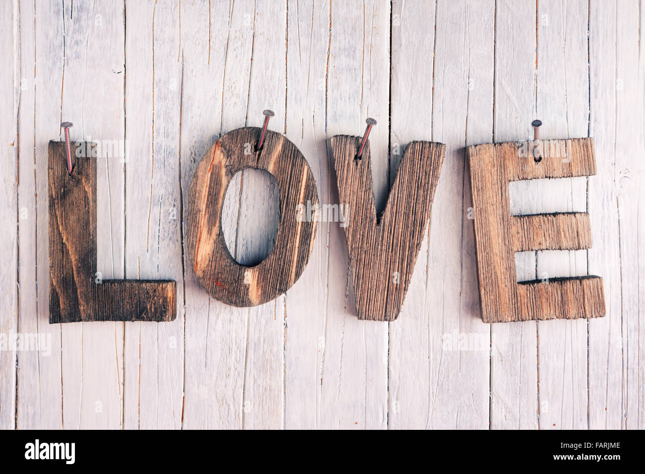 The Word Love In Wooden Letters Nailed On A Rustic Background