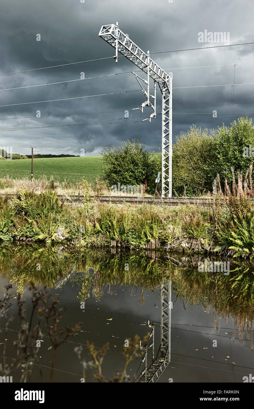 Overhead gantry for electrified train lines UK in countryside with canal in foreground - Stock Image