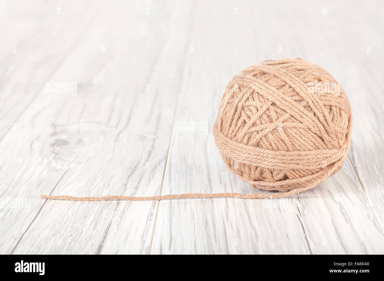 Wool ball on a white wooden background. - Stock Image