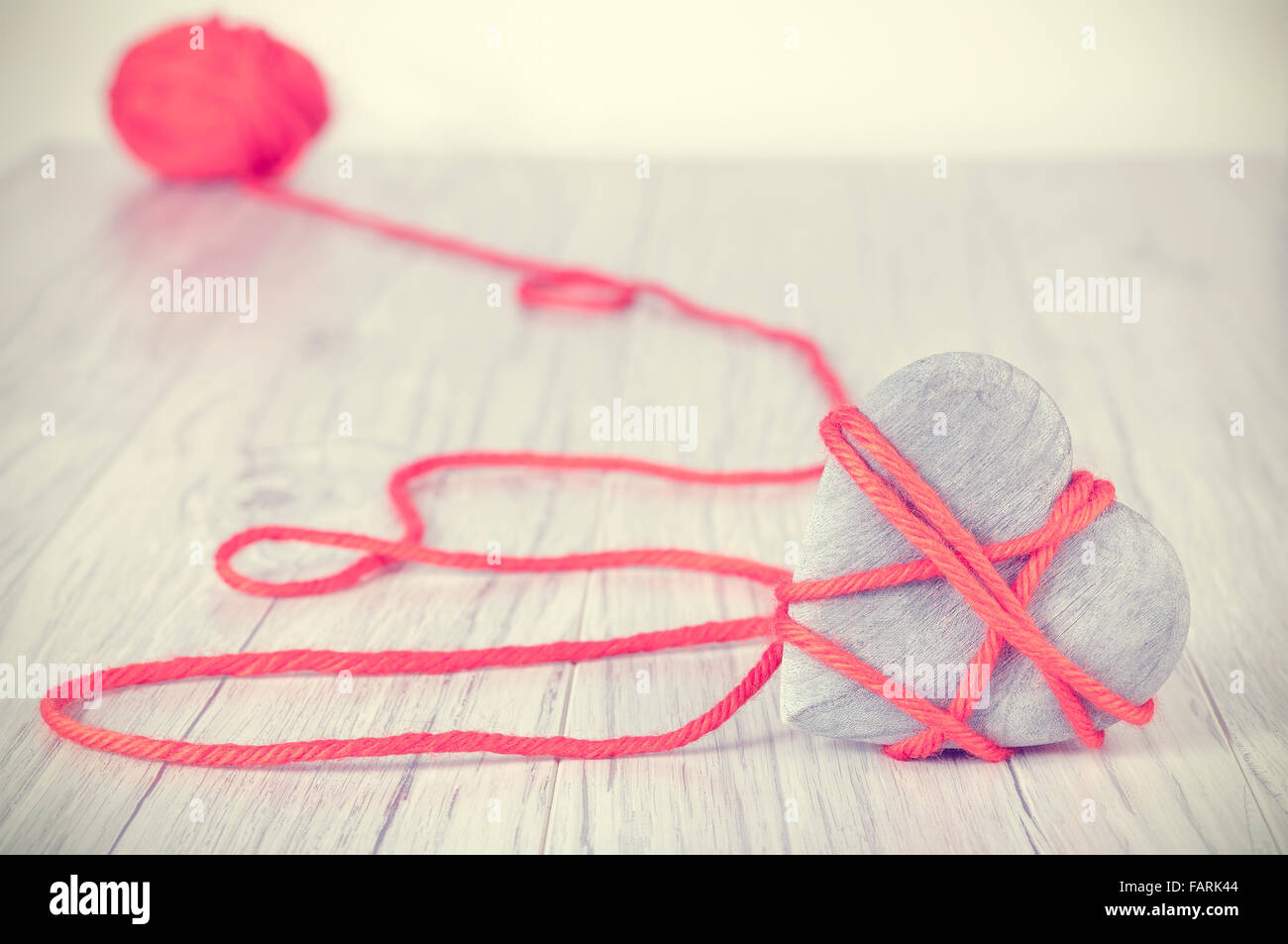 Retro toned wooden heart tied with red yarn, concept picture. - Stock Image