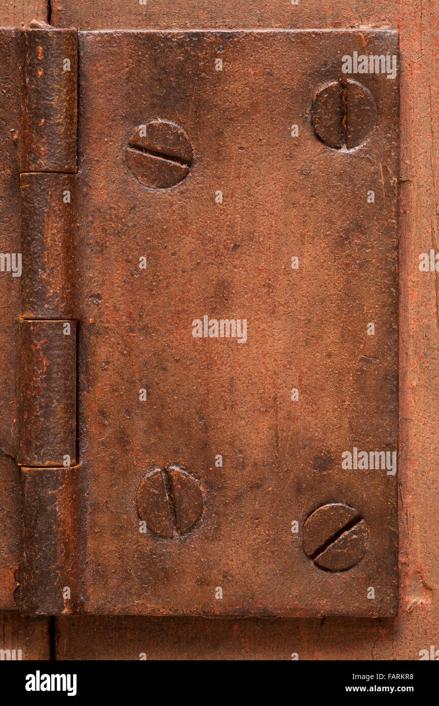 old rusted hinge with screws or vintage background - Stock Image