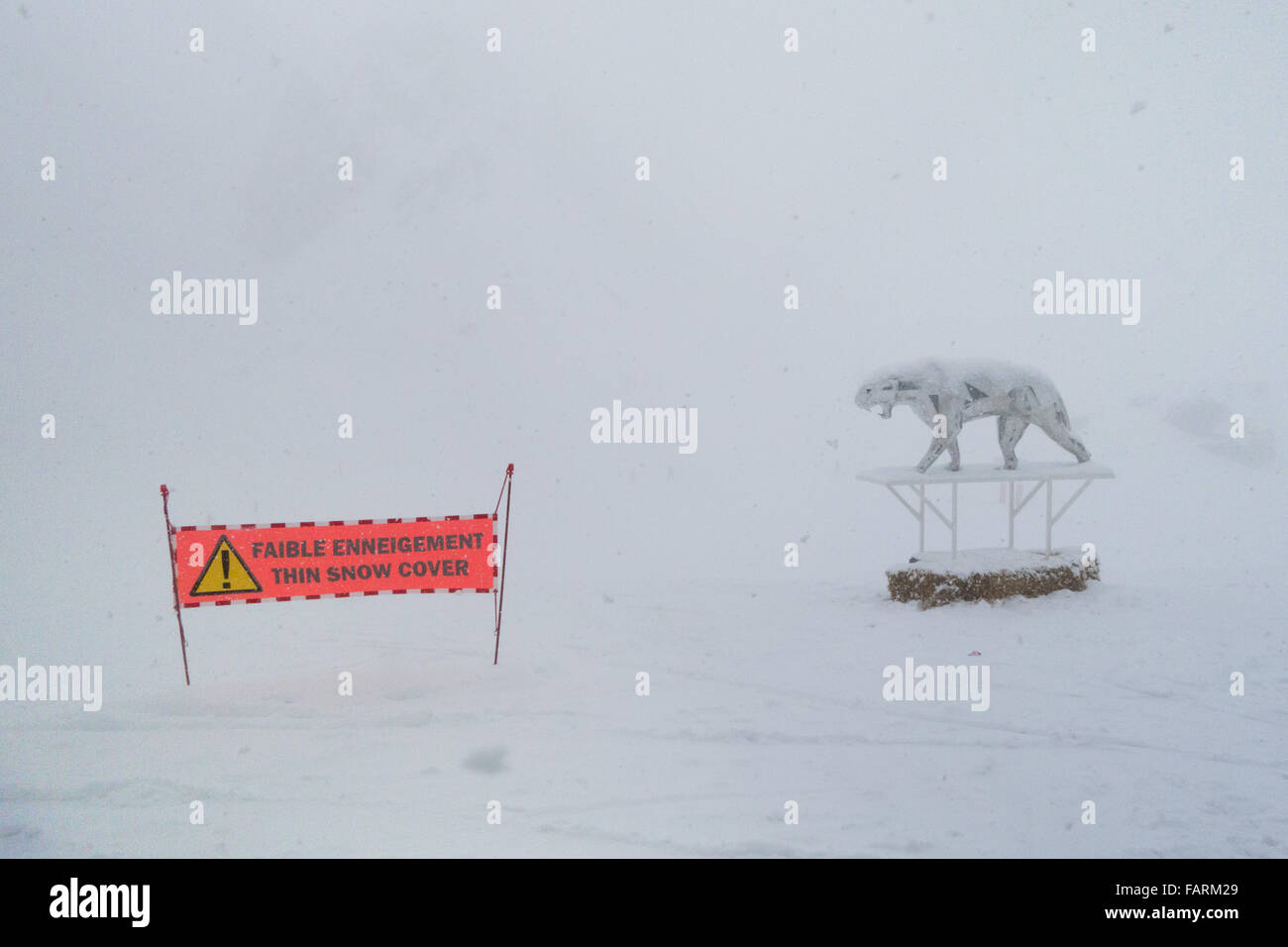 Courchevel, France - thin snow cover sign next to Orlinski summit sculpture in much needed falling snow - Stock Image