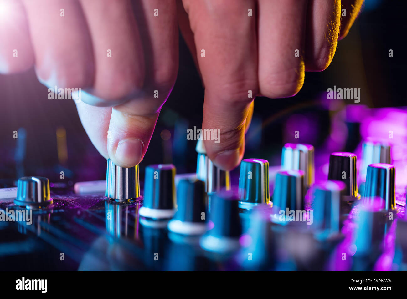 Detail of dj's hands operating on console - Stock Image