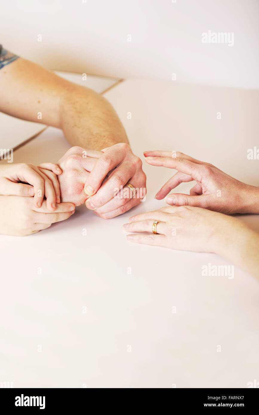 Child holds the hands of mother and father during a fragmented and strained relationship, bringing the family together Stock Photo