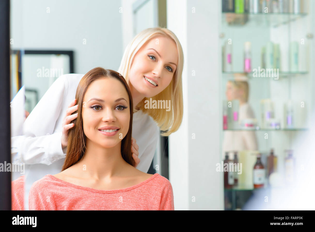 Stylist is showing hairdo to her client. - Stock Image