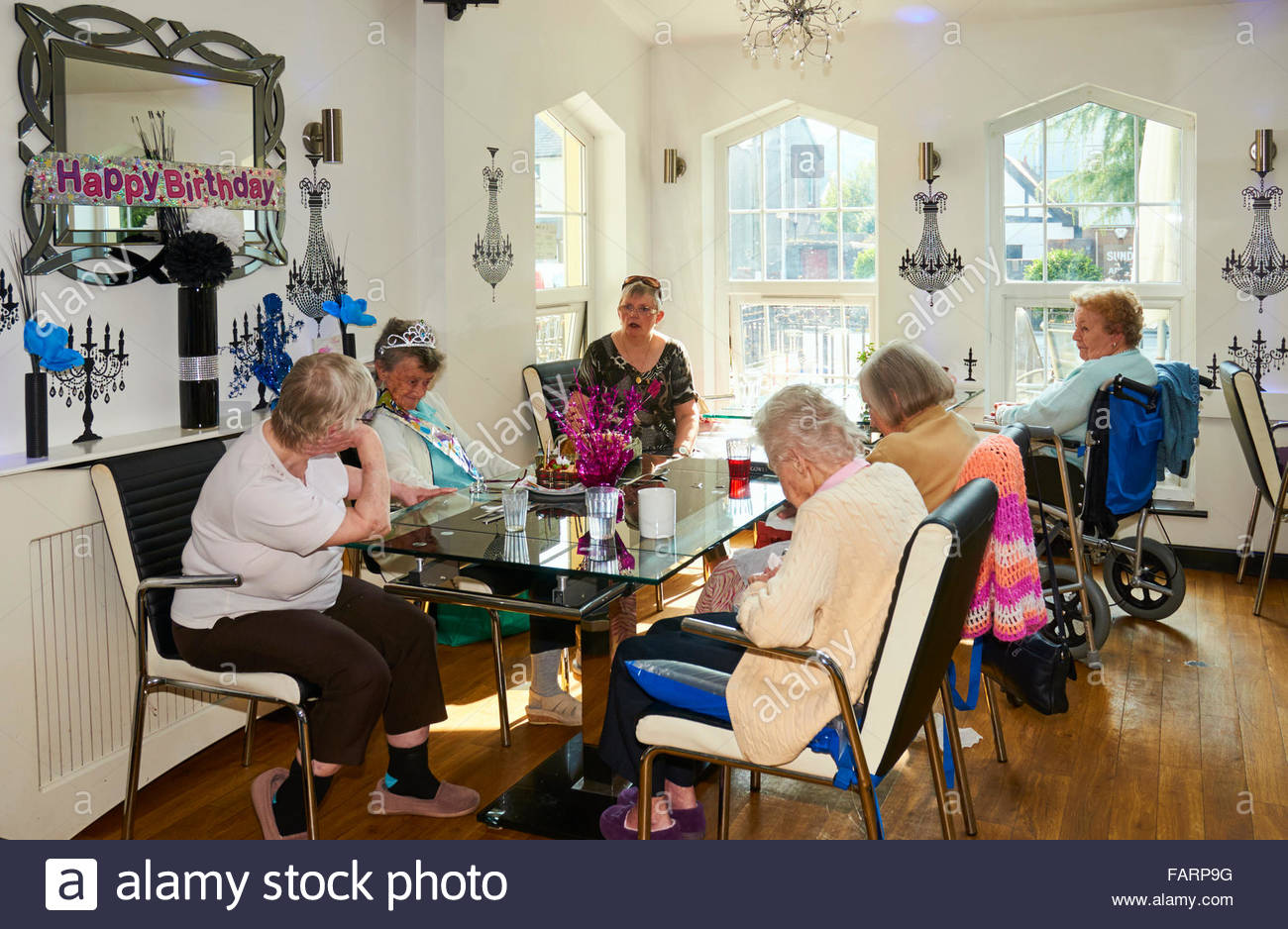 Daughter in law visiting elderly people in a care home having a birthday party - Stock Image