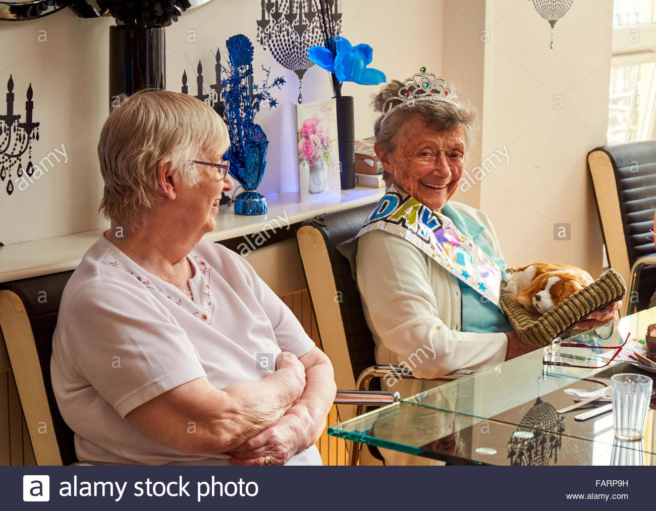 A couple of elderly ladies sitting together in a care home for a birthday party - Stock Image