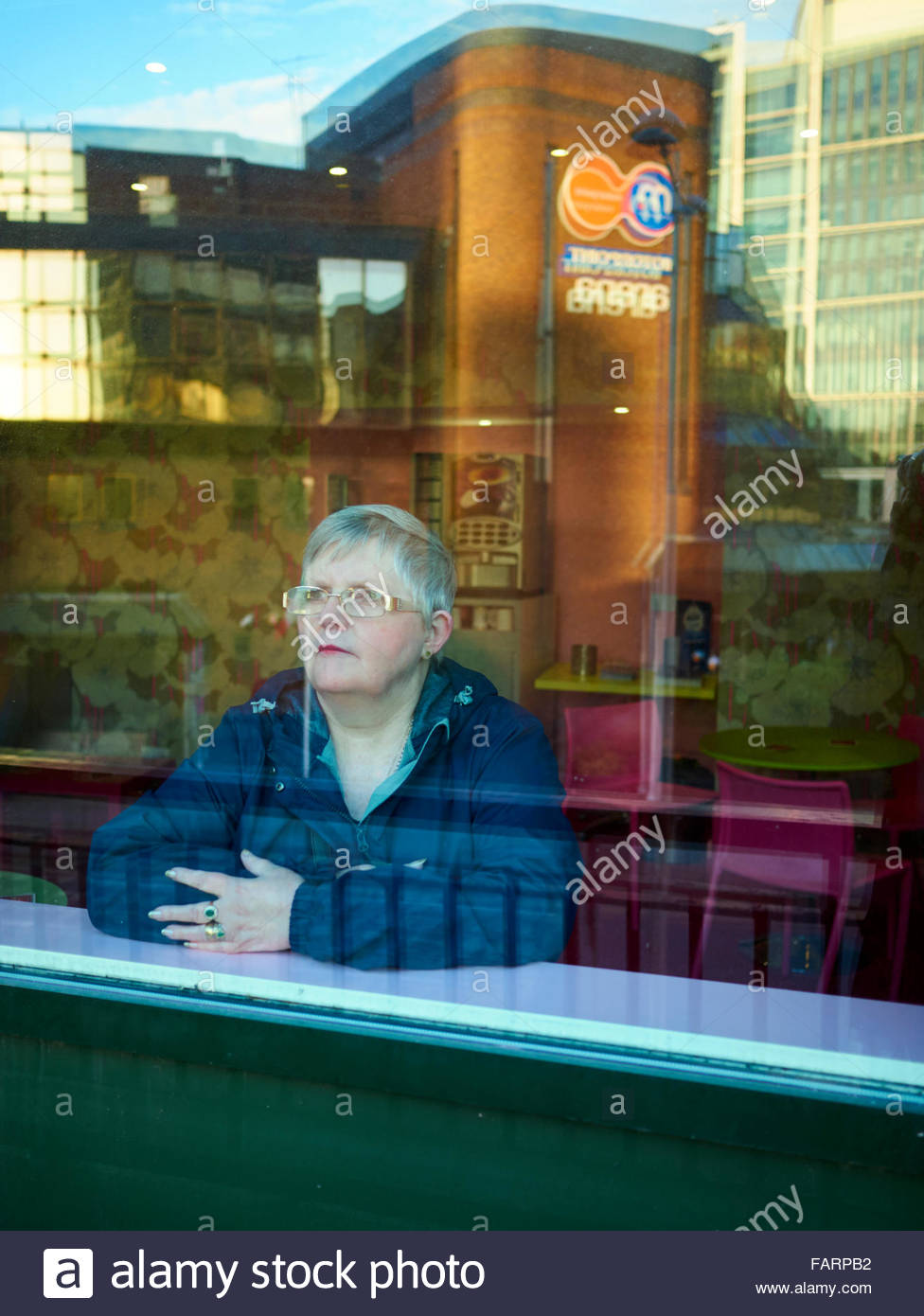 A woman with grey hair and wearing spectacles looking out of a cafe window and in deep thought Stock Photo