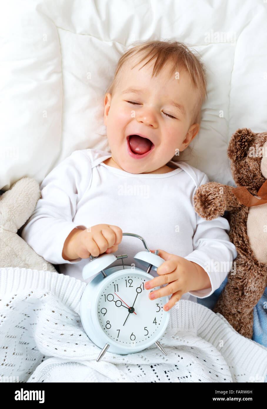 One year old baby with alarm clock - Stock Image