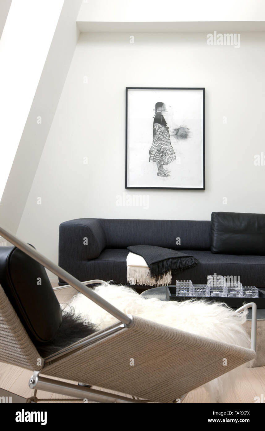 No nonsense Modern apartment in Copenhagen White walls and a wooden floor Art pieces and minimalist style A seating - Stock Image