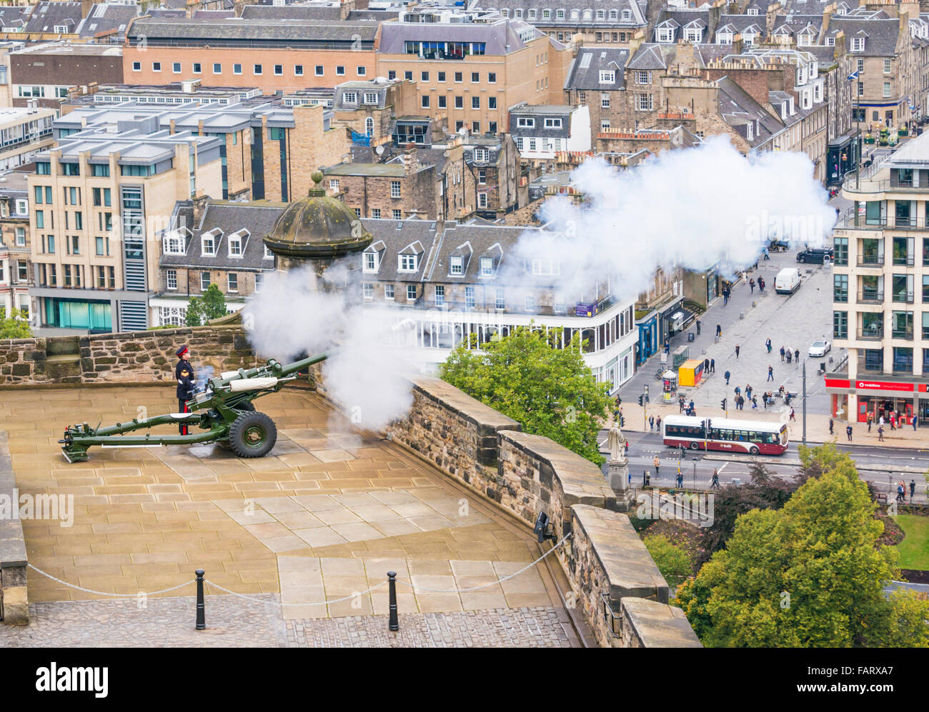 A royal artillery soldier fires the The One O'Clock Gun from Mill's Mount Battery Edinburgh castle Scotland - Stock Image