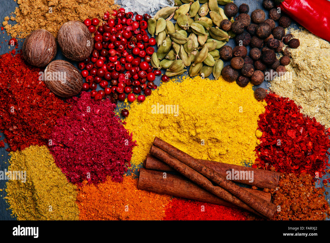 assortment of spices seasoning on a black stone - Stock Image
